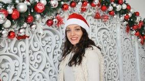 Dentro retrato da moça bonita que veste o chapéu de Santa que olha na câmera no estúdio vídeos de arquivo