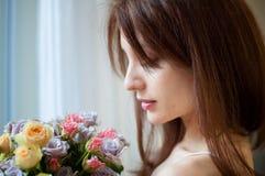 Dentro retrato da posição moreno bonita da mulher perto da janela com um ramalhete das flores que apreciam o cheiro fotos de stock royalty free