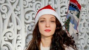 Dentro retrato de la mujer joven sonriente en el sombrero rojo de santa en estudio adornado la Navidad almacen de video