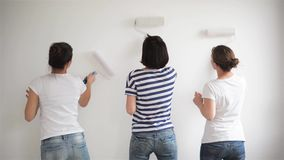 Dentro retrato de tres muchachas que pintan las paredes en el plano con los cristales de exposición Opinión trasera las mujeres j almacen de video
