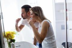 Dents de brossage de couples attrayants dans le matin ensemble image libre de droits