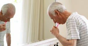 Dents de brossage d'homme supérieur avec la brosse à dents dans la salle de bains banque de vidéos