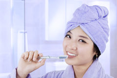 Dents de brossage de femme asiatique attirante image libre de droits