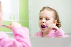 Dents de brossage de fille d'enfant dans la salle de bains Image libre de droits