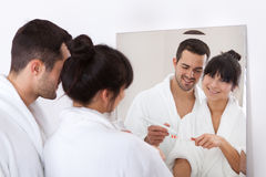 Dents de brossage de jeunes couples photographie stock libre de droits