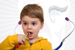 Dents de brossage de Little Boy sur le fond blanc Images stock