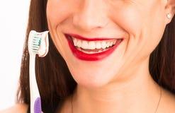 Dents de brossage merveilleuses de femelle adulte de sourire de femme attirante aussi images stock