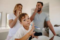 Dents de brossage de petit garçon avec ses parents images libres de droits