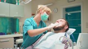 Dents de examen de dentiste féminin du patient masculin, regards à l'appareil-photo clips vidéos