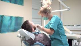Dents de examen de dentiste féminin du patient masculin Tir de glisseur, droite clips vidéos