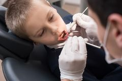 Dents de examen de dentiste pédiatrique de patient de garçon dans la clinique dentaire utilisant les outils dentaires - sonde et  Images stock