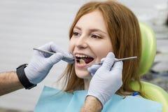 Dents de examen du ` s de fille de dentiste dans la clinique Problème dentaire santé photos stock