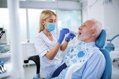 Dents de examen de jeune dentiste d'un patient plus âgé images stock