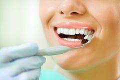 Dents de femme et un miroir de bouche de dentiste photos libres de droits