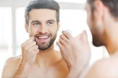 Dents de nettoyage avec le fil dentaire Photographie stock libre de droits
