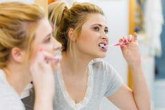 Dents de nettoyage de brossage de femme dans la salle de bains Image libre de droits