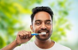 Dents de nettoyage d'homme indien au-dessus de fond naturel images libres de droits