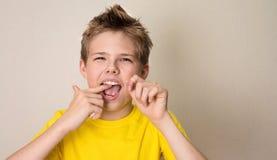 Dents flossing de garçon Portrait en gros plan de garçon de l'adolescence avec la Floride dentaire photo libre de droits