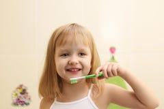 Dents propres mignonnes de petite fille Image stock