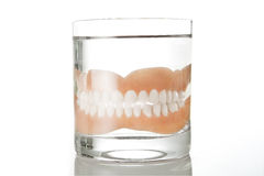 Denture in a glass of water. A glass of water with denture inside on white background royalty free stock images