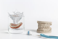 Denture hygiene concept with glass and toothbrush. Dentures hygiene concept displaying mold falling into glass of water and pair of toothbrushes on white Stock Photography