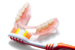 Denture and toothbrush. Denture jaw and tooth brush close up on a white background Stock Photo