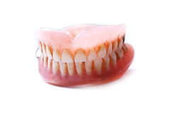 Denture on a white background. Dirty dentures closeup on a white background Royalty Free Stock Images