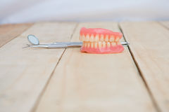 Dentures and dental tools on wooden table Royalty Free Stock Images