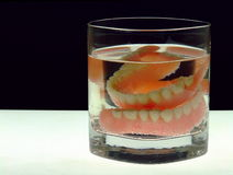 Dentures in a Glass. A full set of dentures soaking in a glass with bubbles Stock Image