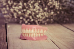 Dentures on wooden table and flower Stock Photo