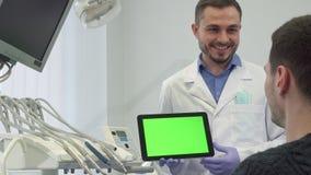 Dentystów explaines coś na ekranie jego męski pacjent zdjęcia stock