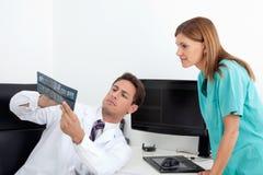Dentysta Analizuje promieniowanie rentgenowskie Z asystentem Zdjęcie Stock