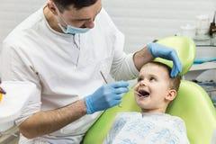 Dentysta egzamininuje chłopiec ` s zęby w klinice Stomatologiczny problem Obraz Royalty Free