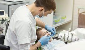 Dentysta egzamininuje chłopiec ` s zęby w klinice Stomatologiczny problem Obrazy Stock