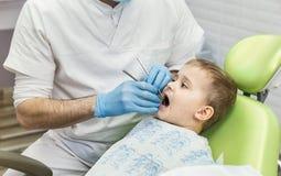 Dentysta egzamininuje chłopiec ` s zęby w klinice Stomatologiczny problem Obrazy Royalty Free