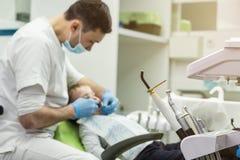Dentysta egzamininuje chłopiec ` s zęby w klinice Stomatologiczny problem Fotografia Stock
