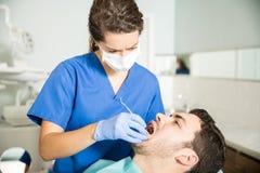 Dentysta Egzamininuje mężczyzna Z Stomatologicznym Carver Przy kliniką zdjęcia royalty free