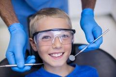 Dentysta egzamininuje młodego pacjenta z narzędziami zdjęcie royalty free