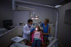Dentysta egzamininuje młodego pacjenta z narzędziami obrazy royalty free