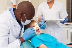 Dentysta egzamininuje pacjentów zęby Zdjęcia Stock