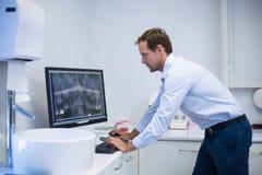 Dentysta egzamininuje promieniowanie rentgenowskie na komputerze w stomatologicznej klinice zdjęcie stock