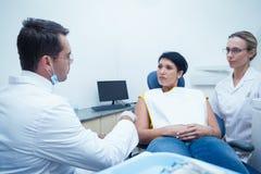 Dentysta i asystent z żeńskim pacjentem Fotografia Stock