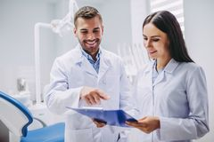 Dentysta i pomocniczy patrzeje schowek zdjęcie royalty free