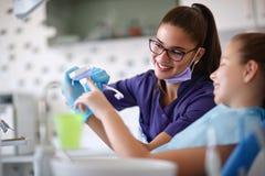 Dentysta kształci małej dziewczynki dlaczego szczotkować zęby fotografia royalty free