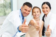 Dentysta lekarka, asystent i mała dziewczynka wszystko uśmiechnięci przy kamerą, zdjęcie stock