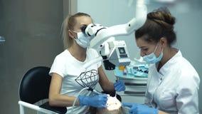 Dentysta lekarka z asystentem w kliniki pracie z odniesienie monitorem zbiory wideo