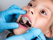 Dentysta, ortodonta egzamininuje troszkę dziewczyny ` s cierpliwych zęby fotografia stock