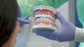 Dentysta pokazuje klienta układ ludzcy zęby zdjęcie wideo