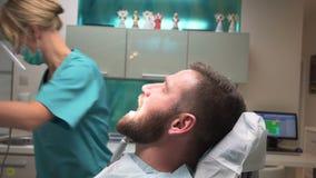 Dentysta przygotowywa stomatologicznych instrumenty i opowiada z pacjentem steadicam zbiory wideo