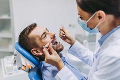 Dentysta sprawdza cierpliwych zęby obraz royalty free